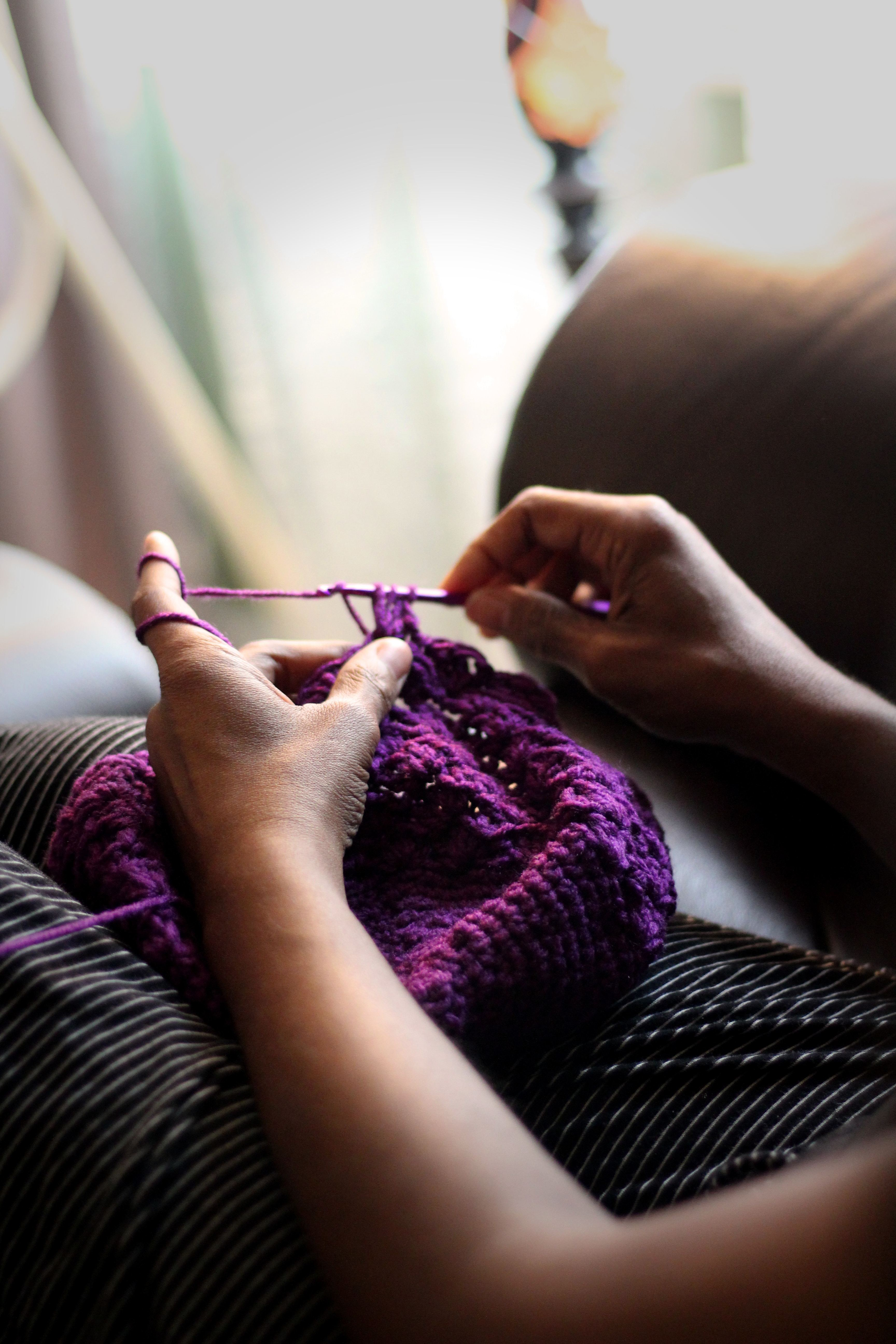 Lady crocheting a purple piece of fabbric